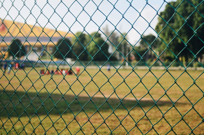 People On Soccer Field Seen Through Chainlink Fence