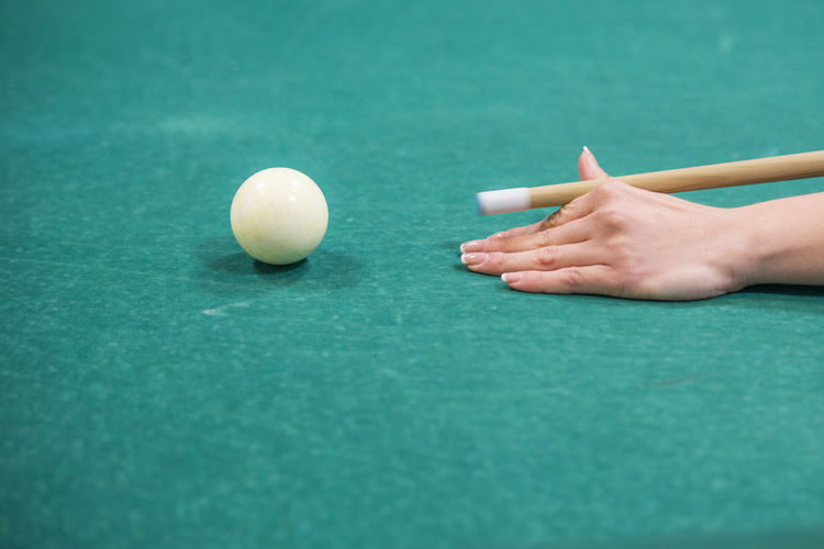 Cropped hand playing pool on table