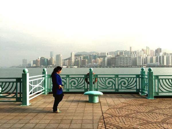 Hong Kong Harbour Woman Fence Blue Green Turquoise Skyline
