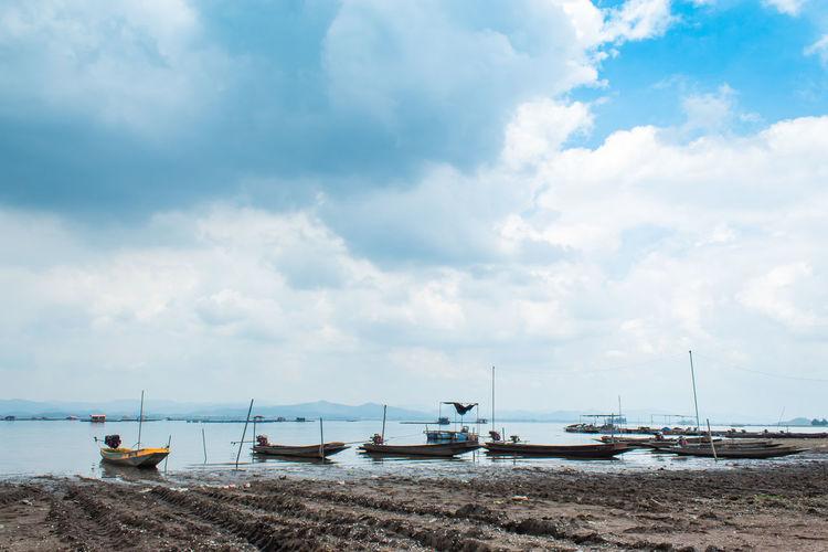 Sailboats moored at beach against sky