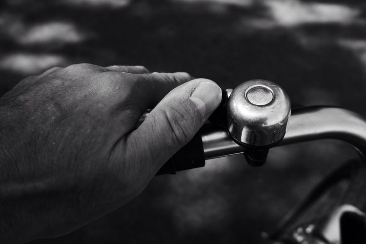Cropped image of hand ringing bicycle bell