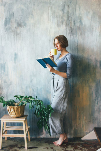 Woman reading book against wall