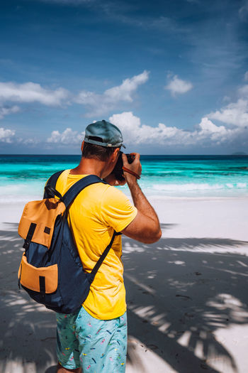Rear view of man photographing with camera while standing at beach