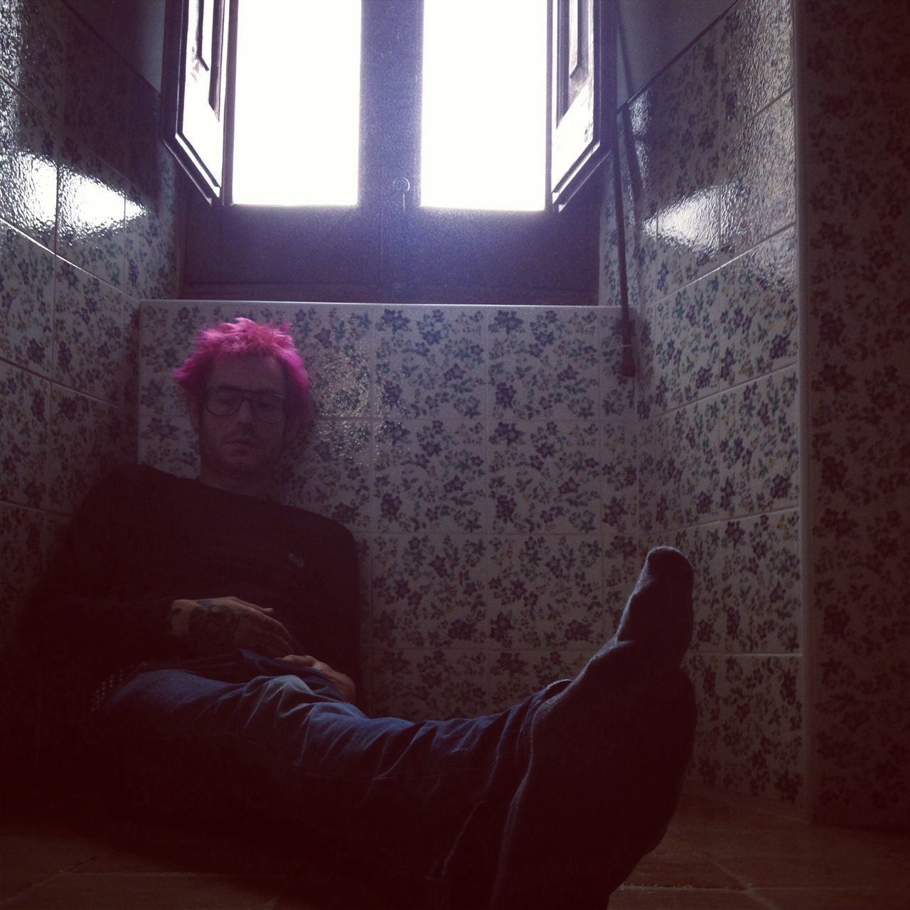 Man sitting on tiled floor at home