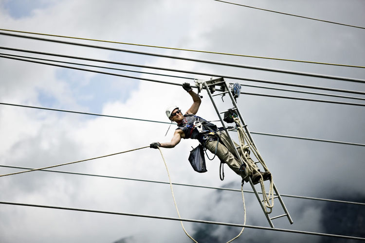 Low angle view of man working on cable against sky