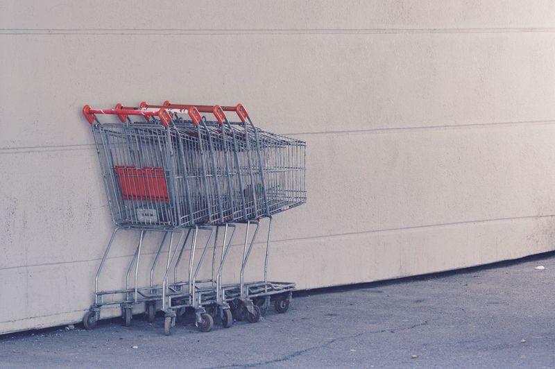 Shopping carts on sidewalk against wall