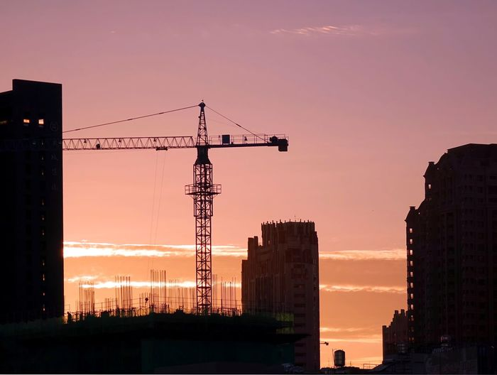 Low Angle View Of Silhouette Crane Against Sky At Sunset