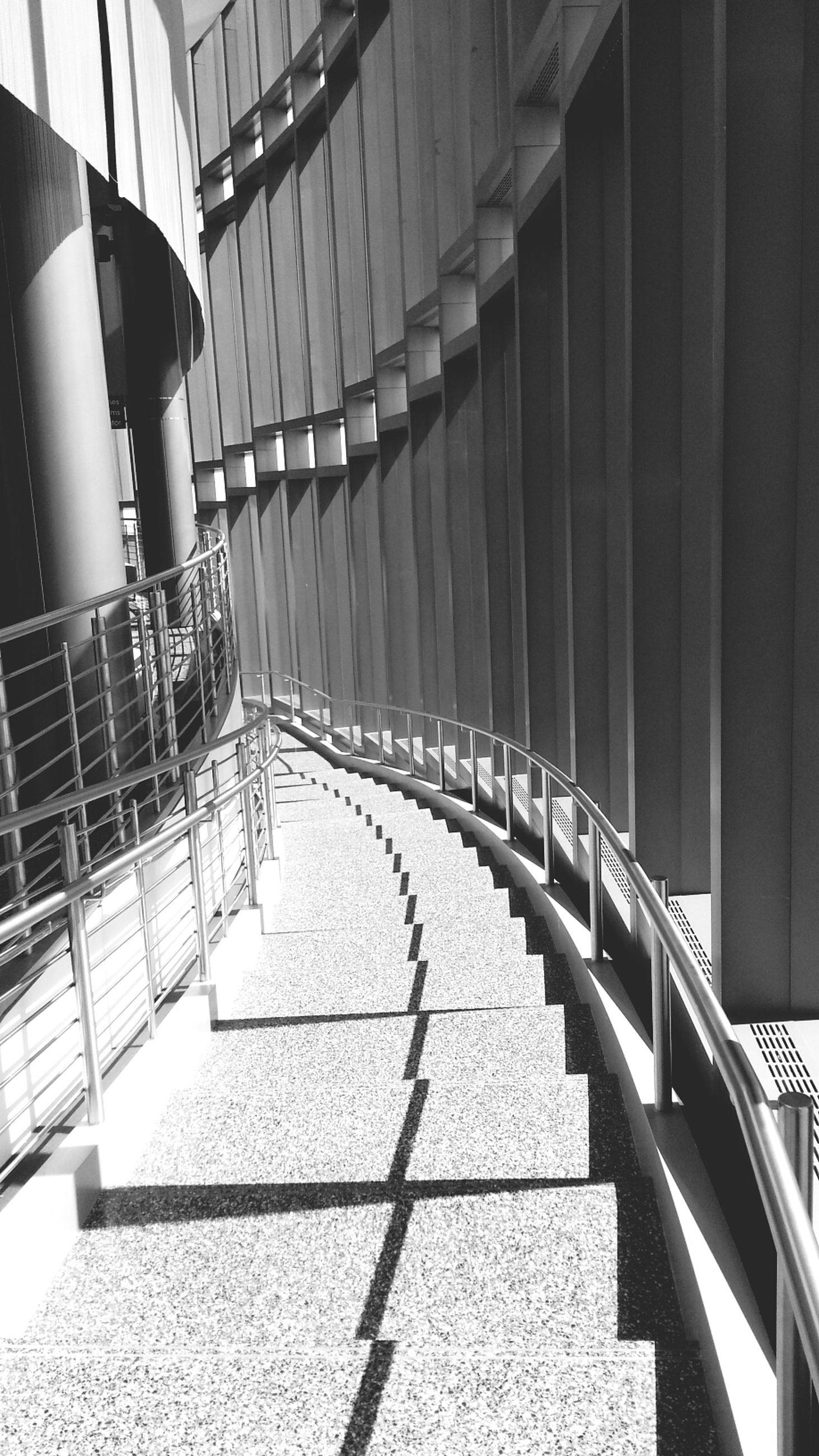 railing, built structure, architecture, the way forward, steps, sunlight, steps and staircases, diminishing perspective, incidental people, walkway, shadow, indoors, transportation, walking, empty, building exterior, vanishing point, day, footpath
