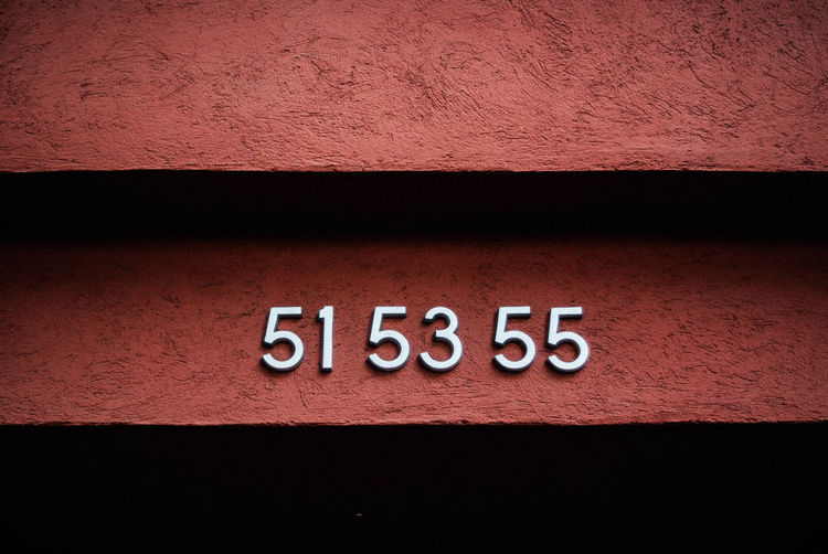 Close-up of number on brown wall