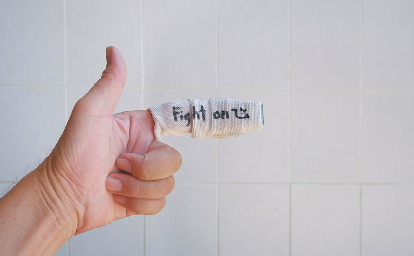 """Close up man's hand with soft splint on forefinger and """"fight on"""" word on surface with blurred white tiles wall background at home, encouragement and health care concept Smile Sign Symbol Face Lifestyle Fight On Text Word Caring Injured Soft Splint Bandage Forefinger Thumb Up Gesture Encouragement Close Up Tile Wall White At Home Copy Space Recuperate Health Care Medical Man Male Human Hand Close-up Finger Thumb"""