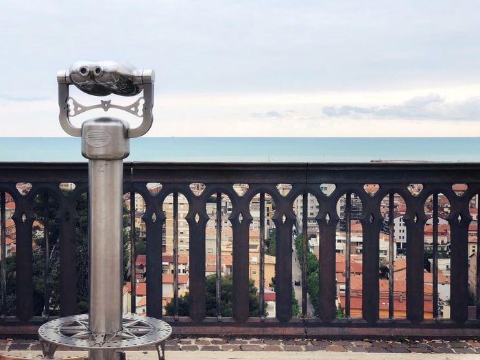 Street light by railing against sky