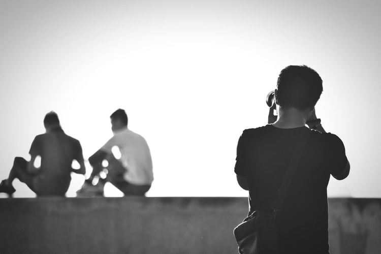 Rear view of man photographing people against clear sky