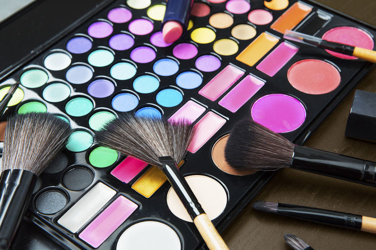 High angle view of make-up and brushes on table