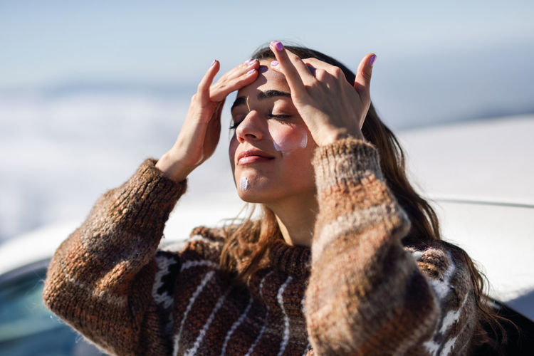 Young woman with eyes closed applying moisturizer while standing outdoors during winter