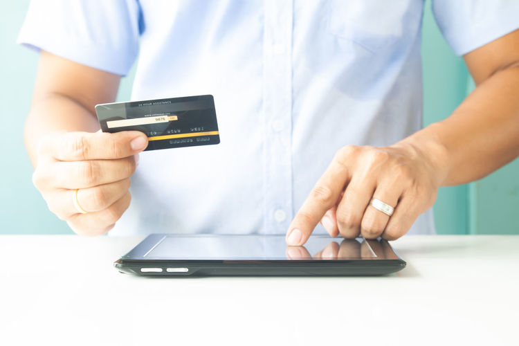 Man hands using tablet and credit card. Online payment. E-business, online banking Hotel Trip Passport Cart Traveler Plastic Concept Entering E-commerce Cvv Ordering Wireless Tax Male Order Debit Smart Security Man Typing RISK Information Data Lifestyle White Phone Ecommerce Keyboard Finance Electronic Internet Store Home Buy Technology Commerce Banking Using Purchase Business Pay Computer Shopping Laptop Hands Holding Payment Online  Card Credit