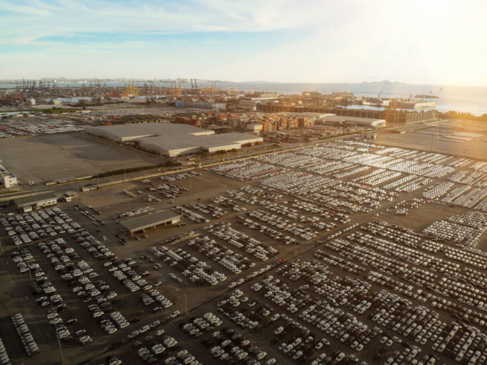 Aerial view of cars parked by shipping yard against sky during sunset