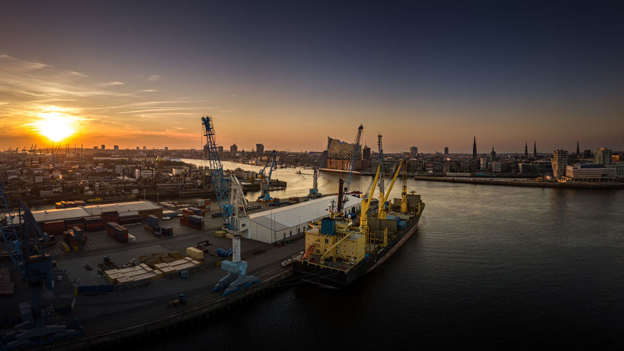 Panoramic view of commercial dock against sky during sunset