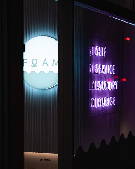 Close-up of illuminated text on glass window