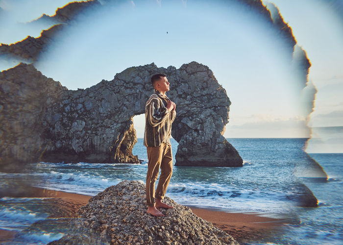 Digital composite image of young man standing on rock at beach