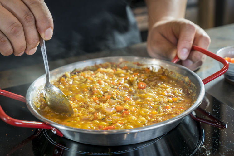 Chef is cooking paella Cooking Food And Drink Meal Paella Rice Spanish Food Chef Restaurant Risotto