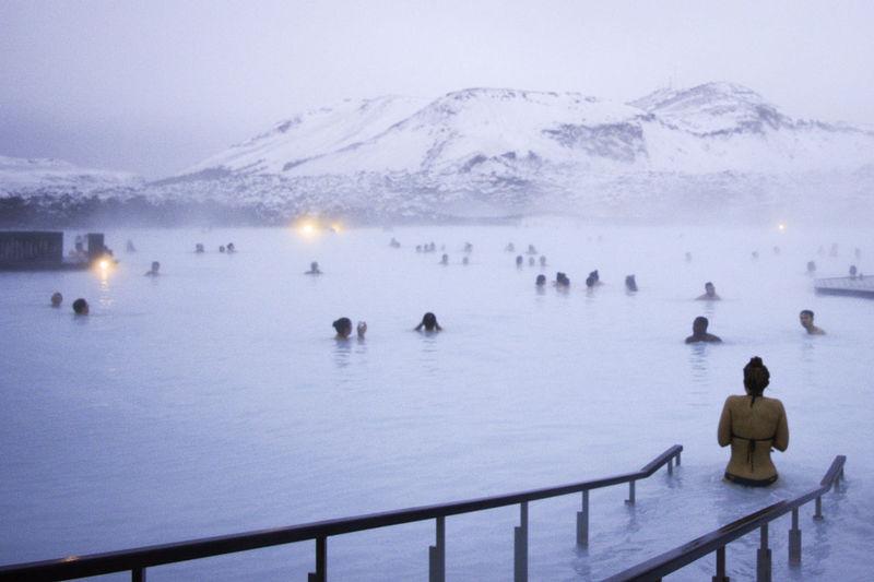 People swimming in lake during winter
