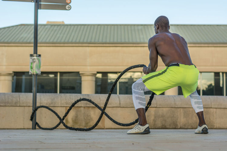 Full Length Of Male Athlete Exercising With Ropes