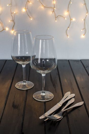 High Angle View Of Wineglasses And Cutlery On Wooden Table Against Wall
