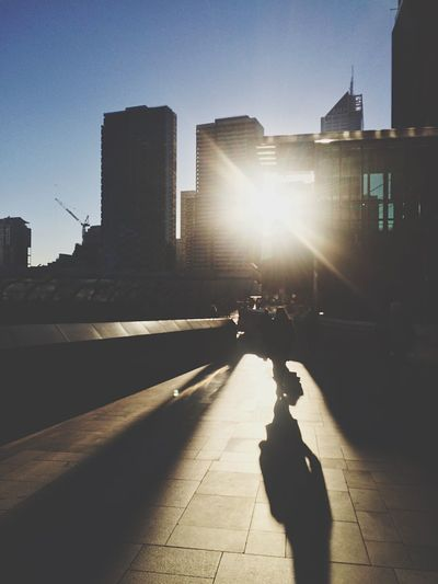 People walking on city street during sunset