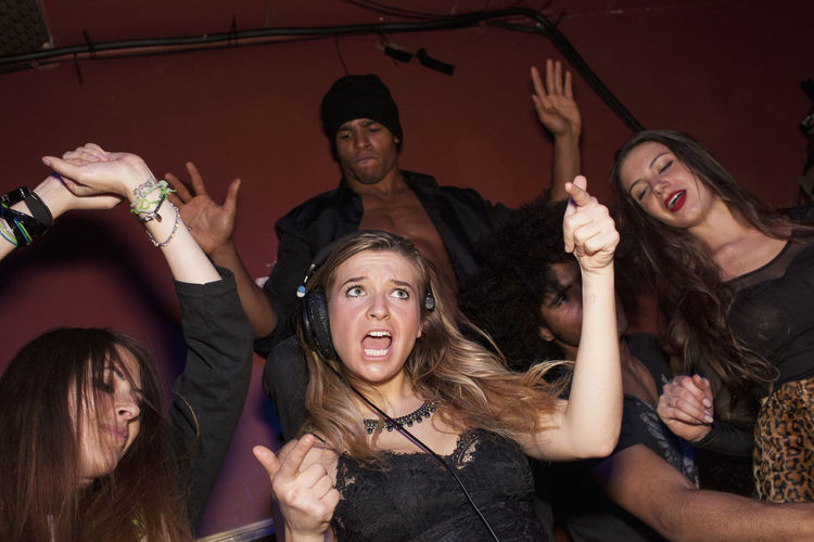 Happy young woman with arms raised at music concert