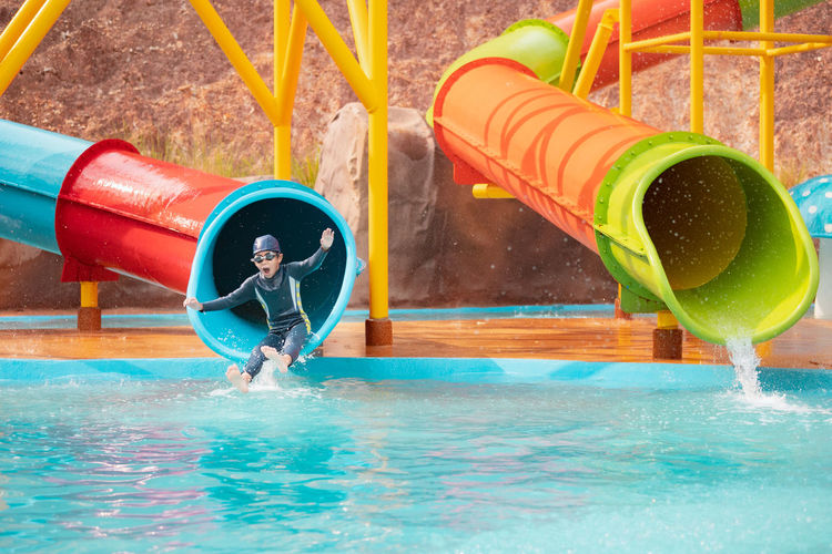 Boy playing in swimming pool at playground