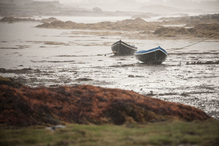 Boats moored on a beach in the rain