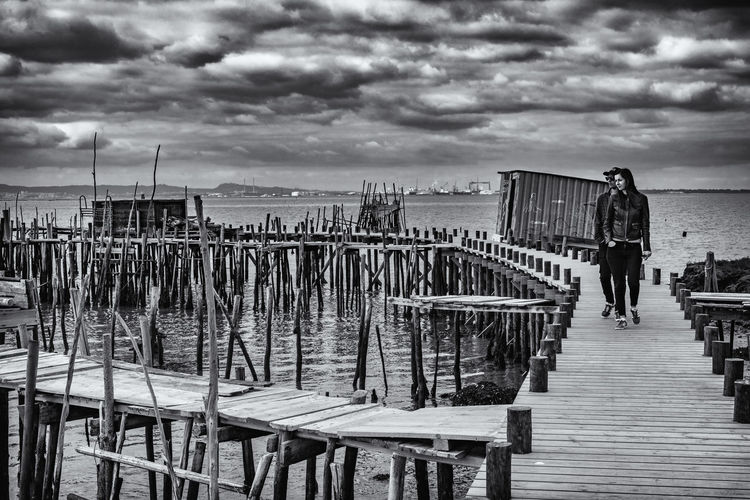 Rear view of woman standing on pier against sky