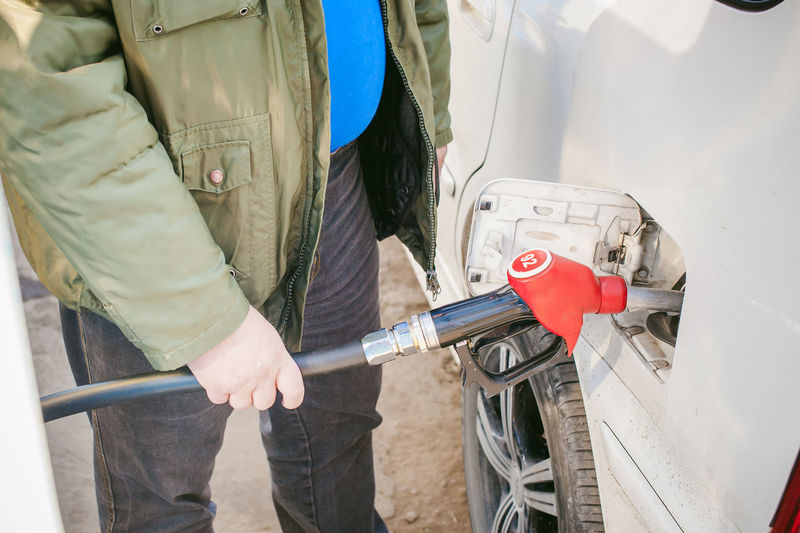 Midsection Of Man Filling Fuel In Car Tank