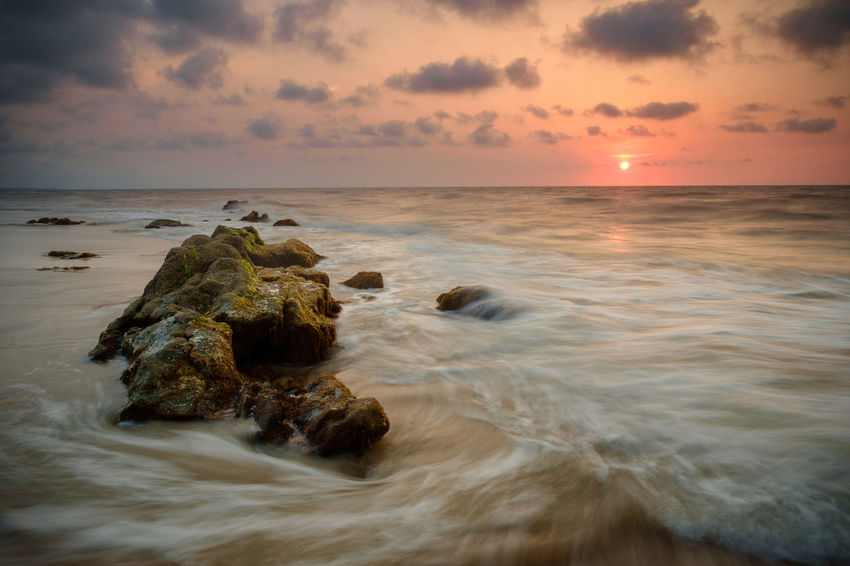 Beach Beautiful Nature Colorful Sky And Clouds Motion Blur Nature No People Orange Sky Outdoors Rocky Beach Sarawak Scenics Sea Seascapes Slow Shutter Sunlight Sunset Waves Streaming Tide Seascape Coastal Feature Horizon Over Water Rocky Coastline Atmospheric Mood