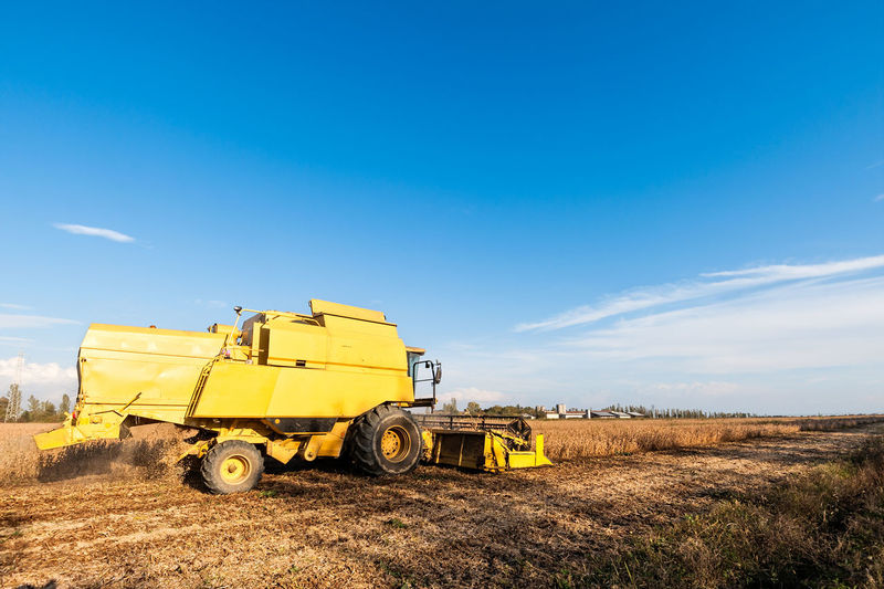 Agricultural machinery on field against blue sky