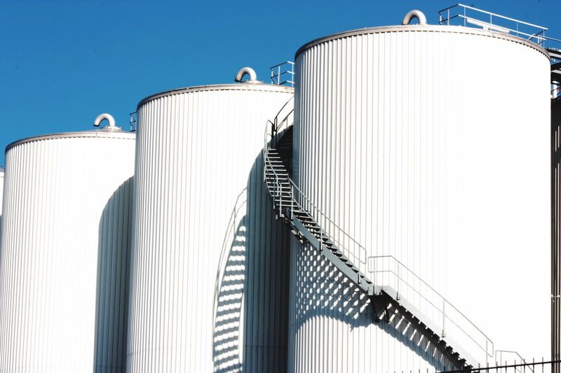 Low Angle View Fuel Storage Tank Against Clear Blue Sky