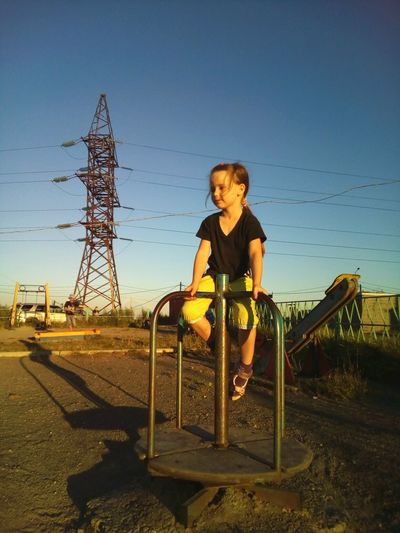 Girl in the sunset light Girl Carousel Whirl Playgarden Summer August Evening Evening Light Powerline High-voltage Tower City Cityscapes Cityscape Street Urban Landscape Urban Enjoy The New Normal