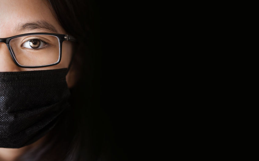 Close-up of cute girl wearing mask against black background