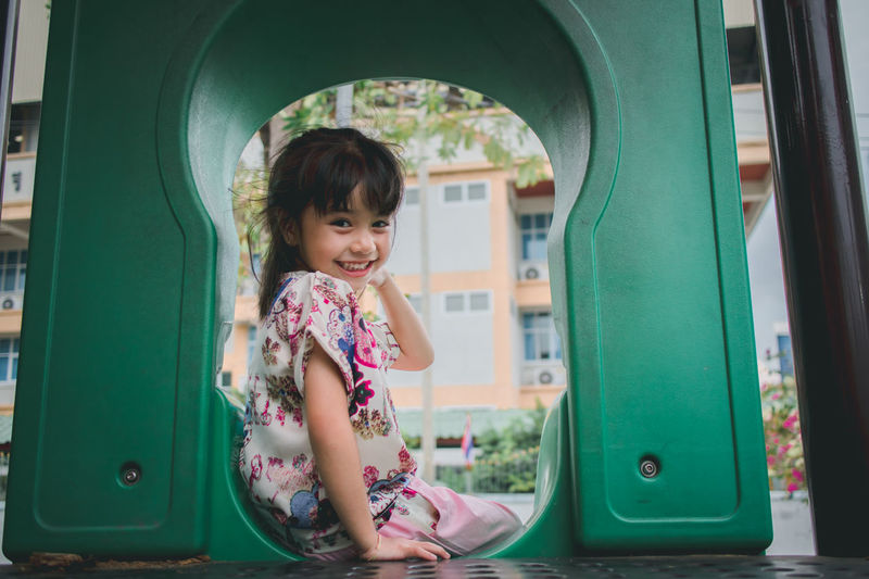little girl smile sitting at playground Innocence Outdoors Child Girl Smiling Lifestyles Fun Outside Playground Little Girl Cute Park Activity Asian  person Portrait Playful Summer Asorable Healthy Young Enjoying Life