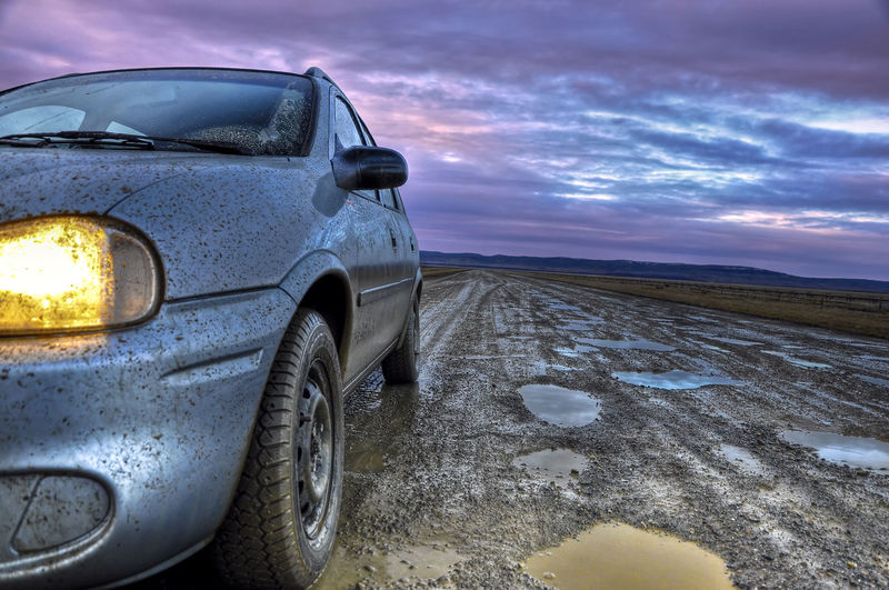 Dirty Car On Muddy Road Against Cloudy Sky During Sunrise