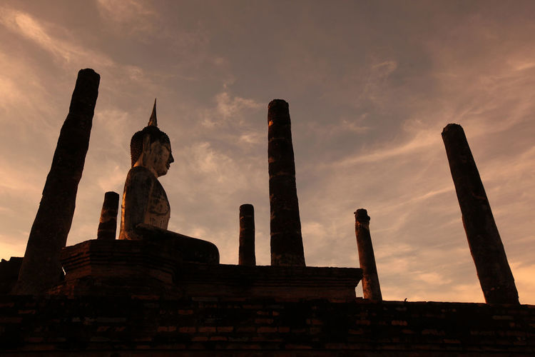 Ancient buddha statue in sukhothai historical park at sunset