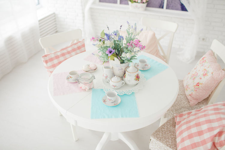 High angle view of crockeries with flower vase on table at home