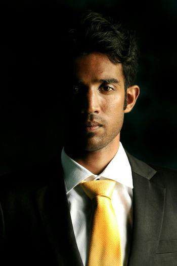 Portrait of businessman standing against black background