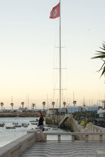 Young woman standing by sea wall, overlooking Cascais Harbour, Portugal. Cascais Portugal Woman Architecture Building Exterior Clear Sky Day Flag Leisure Activity Lifestyles Nature Nautical Vessel One Person Outdoors Patriotism People Real People Sea Sky Summer Sunset Water