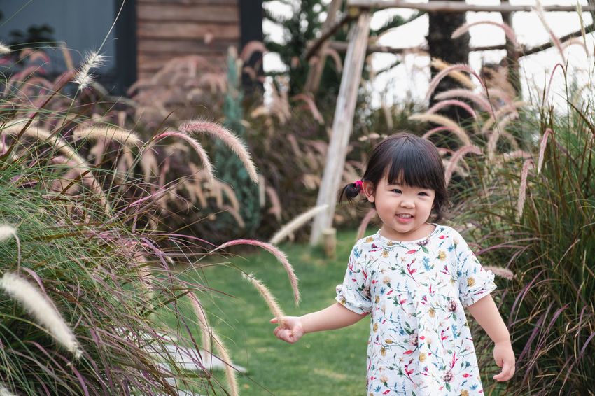 cute girl stand and touching grass EyeEm Best Shots EyeEm Selects Decoration Art Green Color Travel Destinations Sunset EyeEm Nature Lover Spraying Smiling Childhood Happiness Water Cheerful Motion Girls Tree Playing Yard Grassland Formal Garden Garden Path Flowerbed Blooming