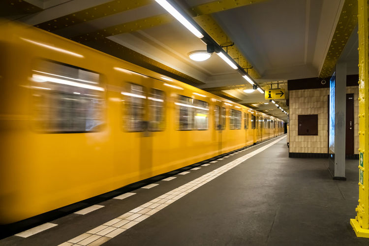 Blurred motion of yellow subway train at railroad station