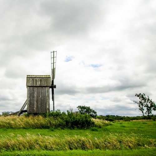 Old-fashioned windmill on field against cloudy sky