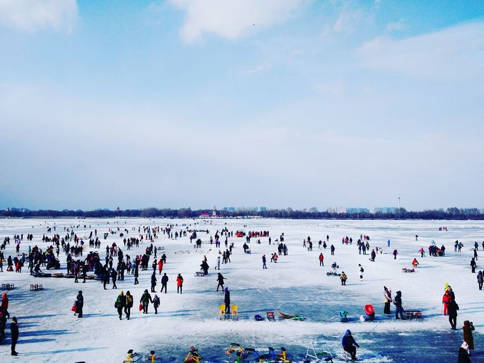 People At Frozen Songhua River Against Cloudy Sky
