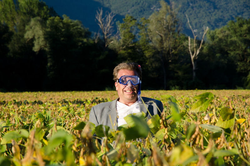 Mature Man Wearing Swimming Goggles And Standing In Farm