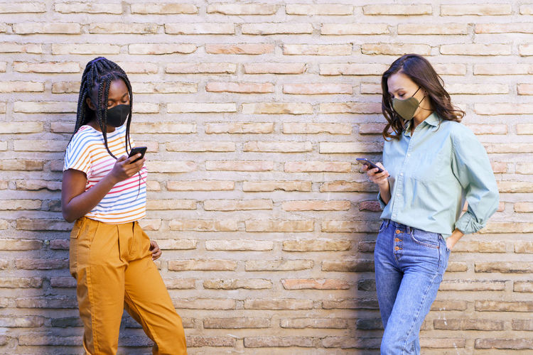 Friends wearing mask using smart phone standing by wall outdoors